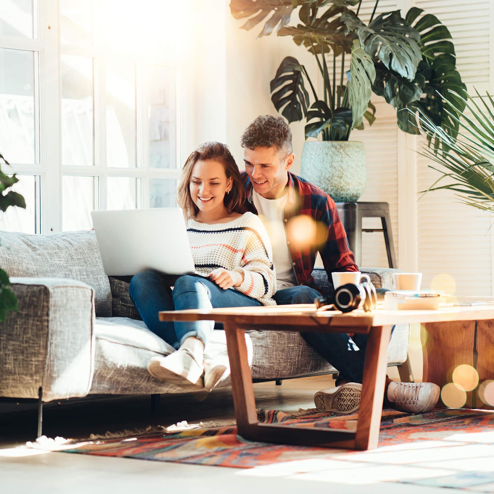 Jong koppel in sofa met laptop - Kapelhoek