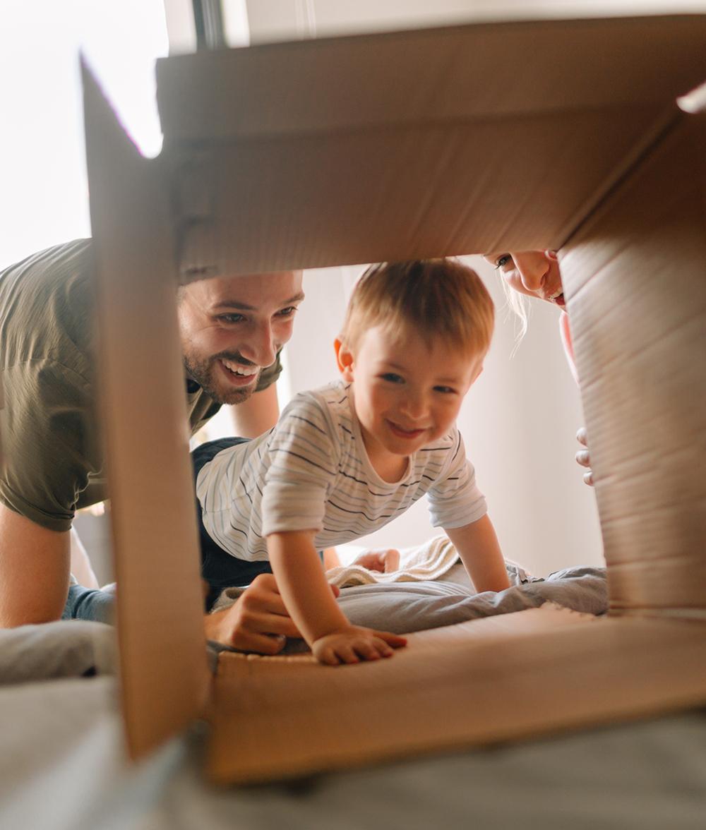 Jong gezin met kindje kruipend kartonne doos - Kapelhoek